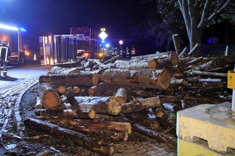 Anhänger eines Holzlasters flog aus der Kurve und kippte um - Baumstämme landeten auf der Straße