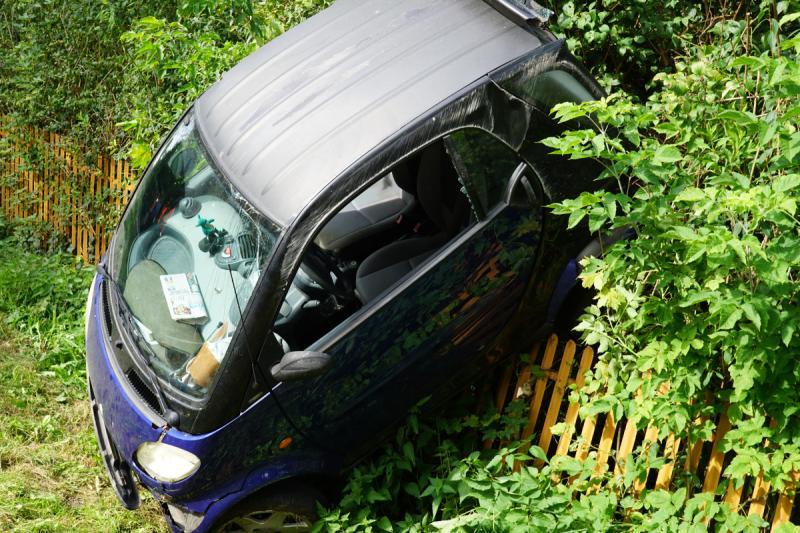 Smart schleudert nach Unfall in Gartenzaun