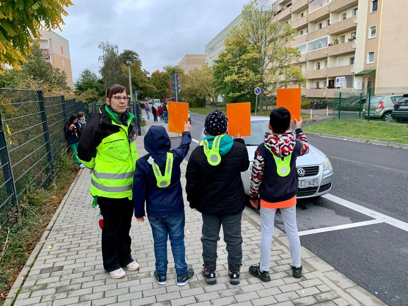 Kinder verteilen Rote Karten an Verkehrsteilnehmer
